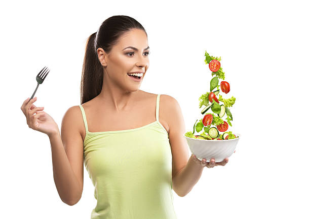 Beautiful, fit young woman holding a bowl of salad stock photo