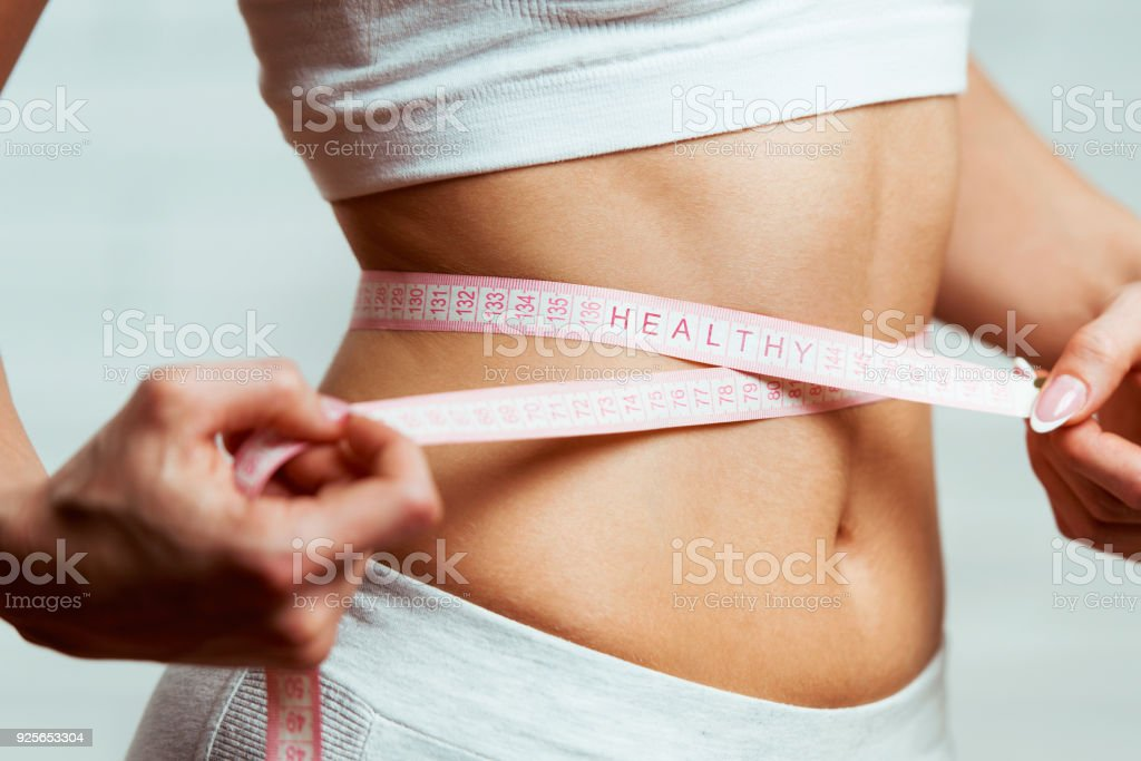 Beautiful, fit, young woman measuring her waist with a measuring tape, with word HEALTHY written on it, close up stock photo
