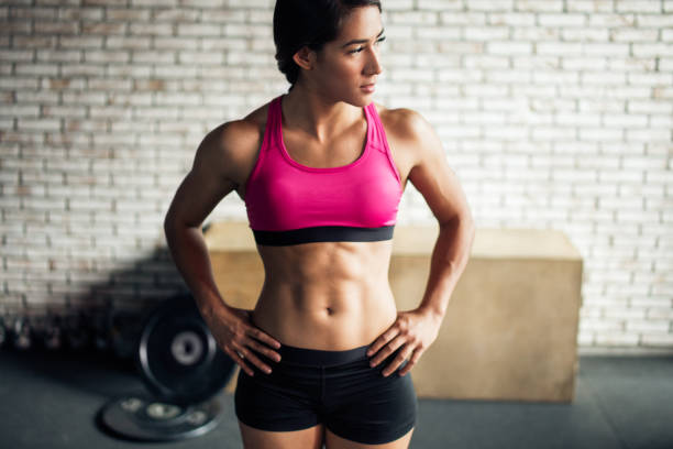 Beautiful fit young woman Beautiful fit young woman in a gym. abdominal muscle stock pictures, royalty-free photos & images