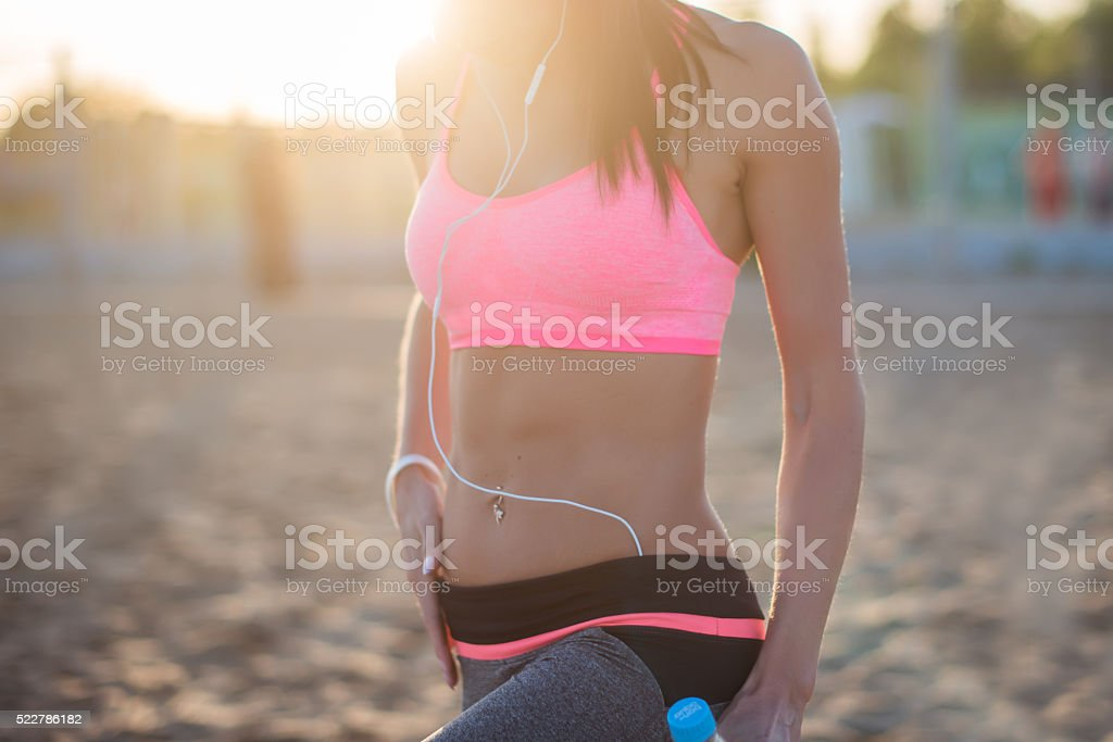 Beautiful fitness athlete woman resting drinking water after work out stock photo