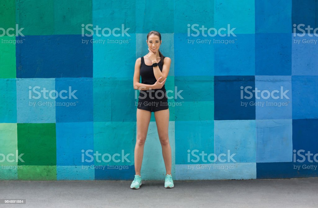 Beautiful fitness girl posing on blue background royalty-free stock photo