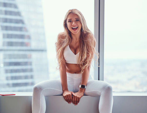 Beautiful fitness model sitting on a window sill in a skyscraper apartment. Beautiful fitness model wearing sportswear sitting on a window sill in a skyscraper apartment. bra stock pictures, royalty-free photos & images