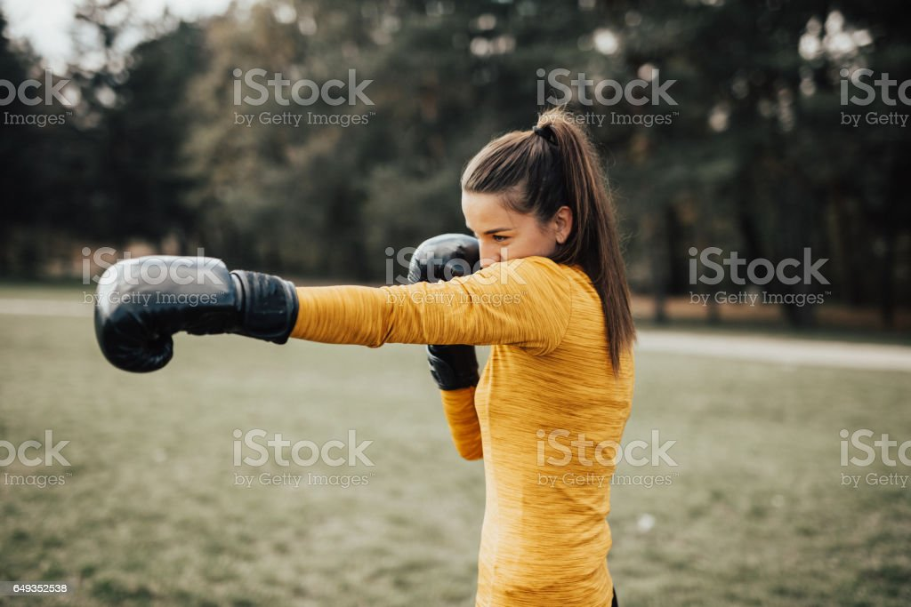 Beautiful Fitness Woman Boxing with Black Gloves stock photo