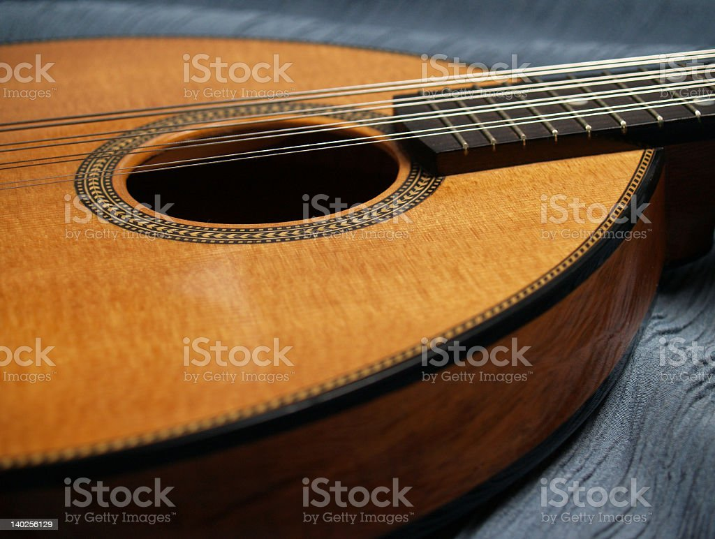 Beautiful Flat-top Mandolin Side View on Blue Fabric stock photo