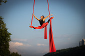 Beautiful and flexible female circus artist dancing with aerial silk on a sky background.