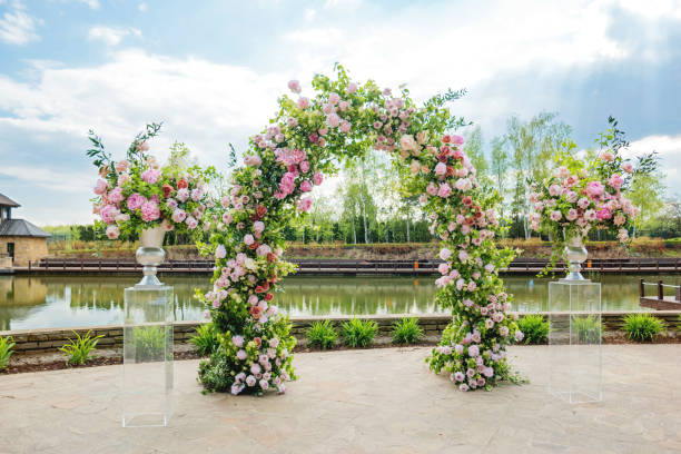 Beautiful floral arch for wedding ceremony. Vases with pink roses and peonies. Wedding set up outdoors in park near pond. stock photo