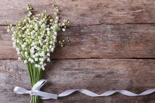 Beautiful floral frame with lilies of the valley flowers on old wooden table. horizontal.