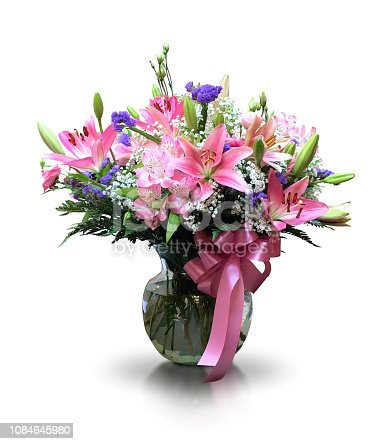 A large fresh vibrant multi colored flower arrangement of pink lily blossoms and buds, white gypsophila, green leaves and a small purple flower cut out with a white background. This beautiful bouquet is decorated with a bright pink ribbon tied around the clear glass vase. There is a faint reflection on the table surface.