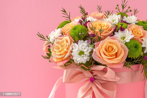 Beautiful bouquet in a red luxury present box, isolated on pink background