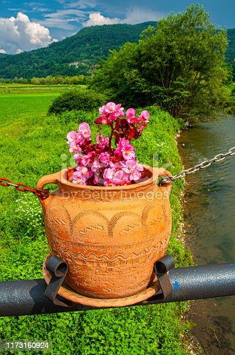 Beautiful flower pots hanging on the fence of the bridge in village Zlokuse, Republic of Serbia, Europe