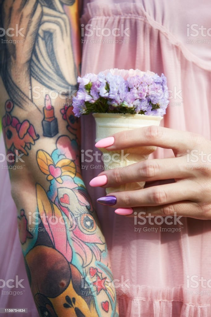 Beautiful flowers in the hands of a girl with tattoos, cosmetics....