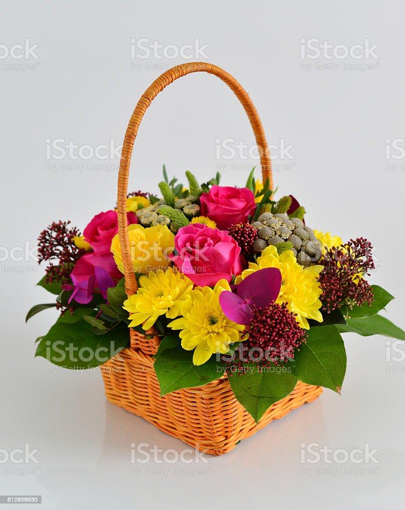 Beautiful flowers in wicker basket on light background stock photo beautiful flowers in wicker basket on light background royalty free stock photo izmirmasajfo