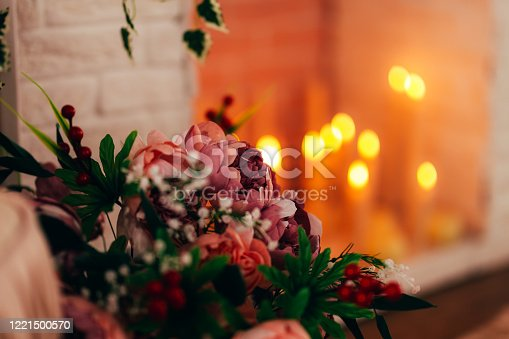 beautiful flowers with burning candles on background, interior