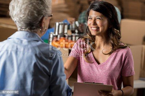 istock Beautiful food bank organizer greets senior volunteer 623503192