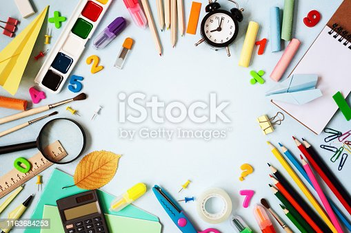 istock Beautiful frame of different stationery, alarm clock and supplies on blue background. Back to school concept. Top view. 1163684253