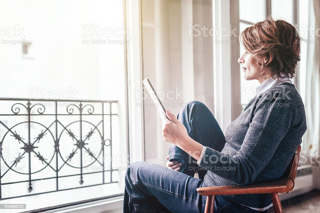 beautiful  french woman reading on digital tablet in Paris apartment stock photo