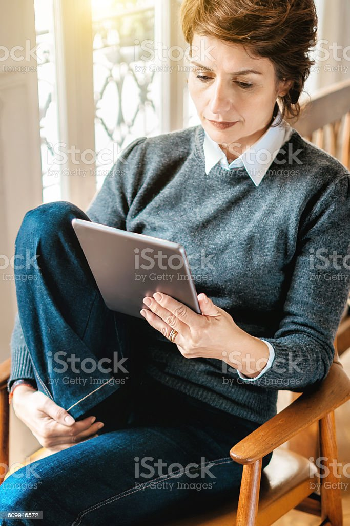 beautiful  french woman reading on tablet in Paris apartment stock photo
