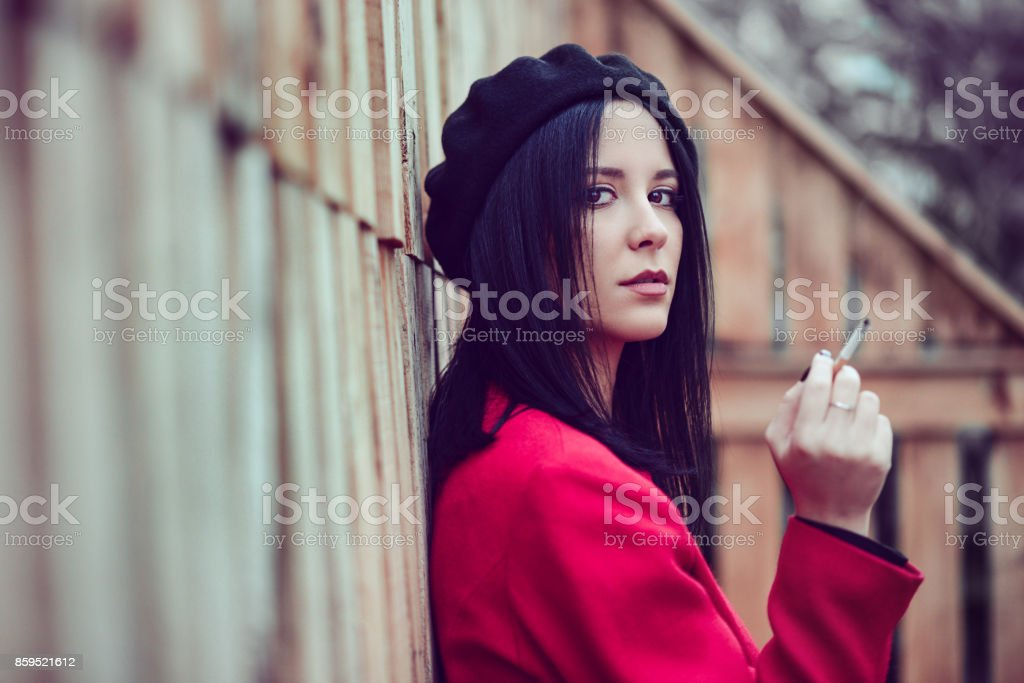 Beautiful French Woman with Beret and red Coat how Smoking Cigarette stock photo