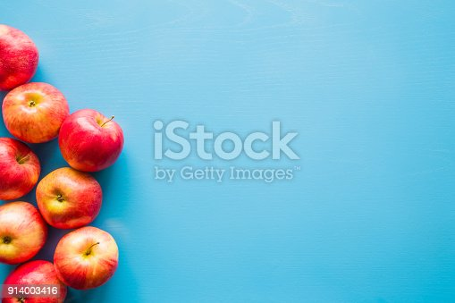 istock Beautiful, fresh, colorful apples on the blue background. Healthy sweet food concept. Mock up for fruits offers as advertising or web background, or other ideas. Empty place for text or logo. 914003416