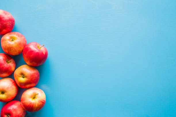 Beautiful, fresh, colorful apples on the blue background. Healthy sweet food concept. Mock up for fruits offers as advertising or web background, or other ideas. Empty place for text or logo. stock photo