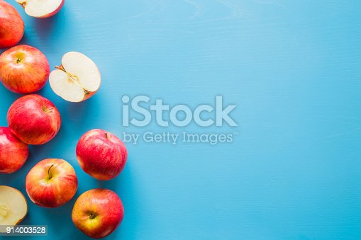 istock Beautiful, fresh, colorful apples on the blue background. Healthy sweet food concept. Mock up for fruits offers as advertising or web background, or other ideas. Empty place for text or logo. 914003528
