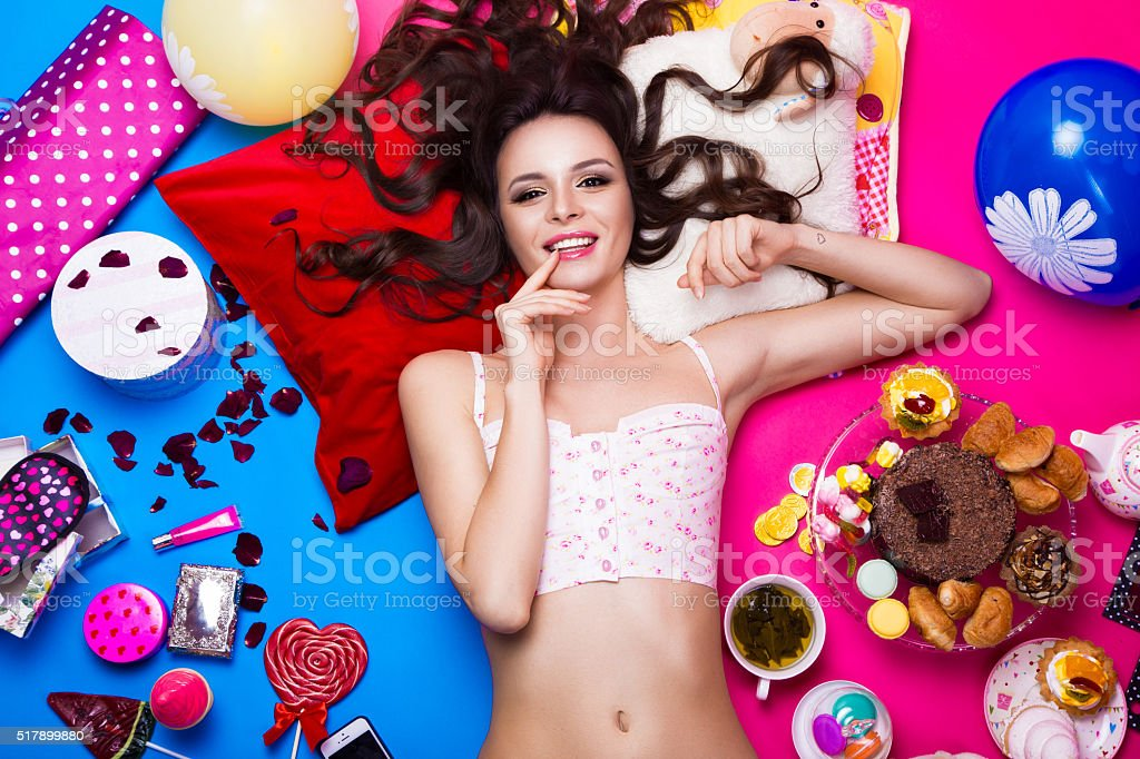 Beautiful fresh girl doll lying on bright backgrounds surrounded by stock photo