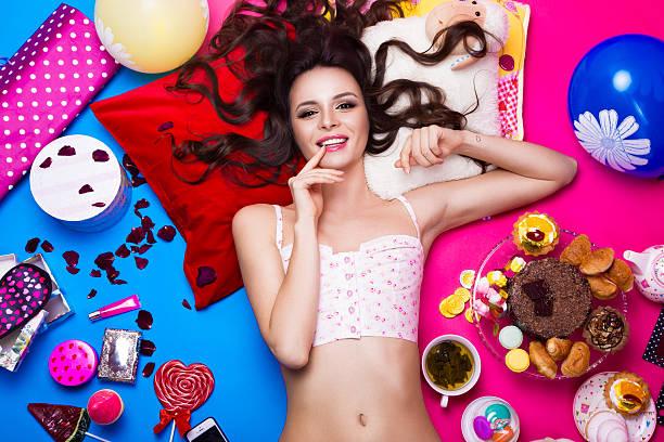 schöne frische girl-puppe auf dem bauch liegen umgeben von hellen hintergrund - make up torte stock-fotos und bilder