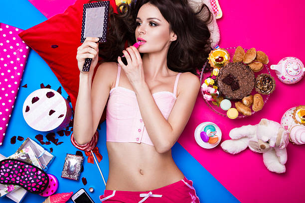 Beautiful fresh girl doll lying on bright backgrounds surrounded by Beautiful fresh girl doll lying on bright backgrounds surrounded by sweets, cosmetics and gifts. Fashion beauty style. Photos shot in the studio. pop musician stock pictures, royalty-free photos & images