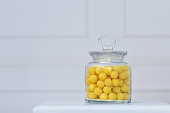 beautiful fresh yellow sugar dragees are stored in a glass transparent jar against the background of the white wall