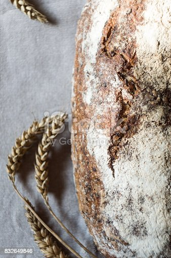 913749618istockphoto Beautiful freshly baked rustic bread and ears of wheat on gray towel 832649846