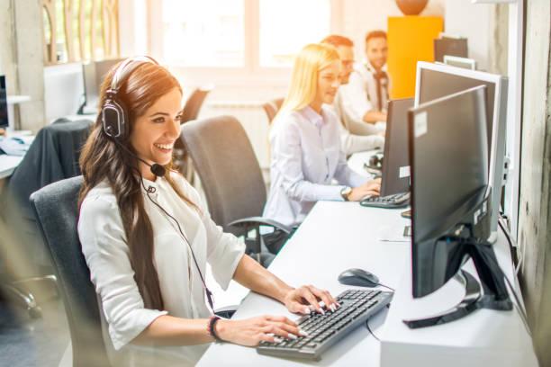 Schöne freundliche Kundenbetreuungsagentur mit Kopfhörern im Gespräch mit dem Kunden, während die Verwendung von Computer im Büro – Foto