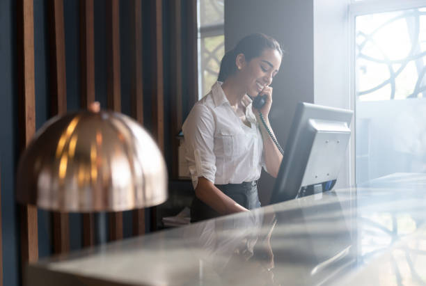 Beautiful friendly hotel receptionist answering a call from a guest Beautiful friendly hotel receptionist answering a call from a guest smiling very happy concierge stock pictures, royalty-free photos & images