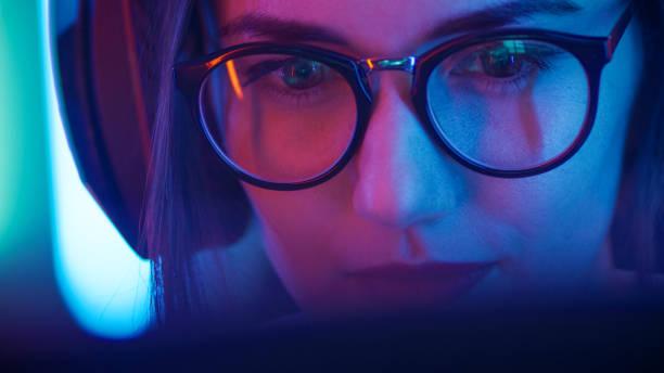 belle amicale pro gamer girl est jeu vidéo gameplay stream, portant des lunettes. geekette attrayante aux couleurs rétro cool néon en arrière-plan. - gamer photos et images de collection