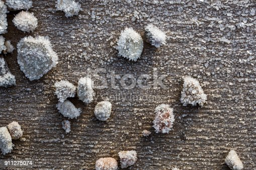 istock Beautiful frost crystals on wood close-up texture background 911275074