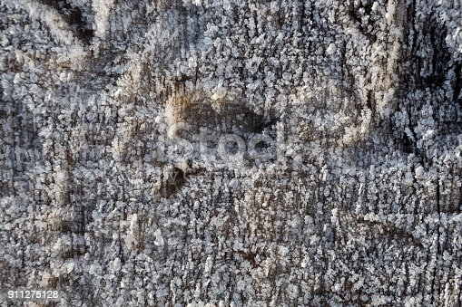 istock Beautiful frost crystals on wood close-up texture background 911275128