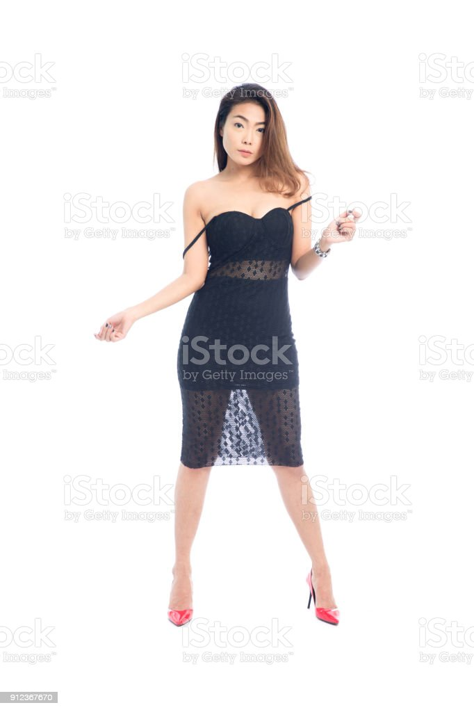 0710913a748 Beautiful full body Asian woman posing in sexy slinky black lace dress  isolated on a white background. - Stock image .