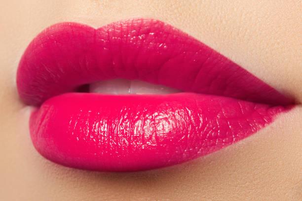 Belos lábios cheio-de-rosa. Batom rosa. Maquiagem e cosméticos - foto de acervo