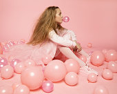 A beautiful funny 10-year-old girl, long fluffy hair in fashionable clothes sits on pink background in the Studio among balloons and inflates bubble of chewing gum. The concept of the celebration.