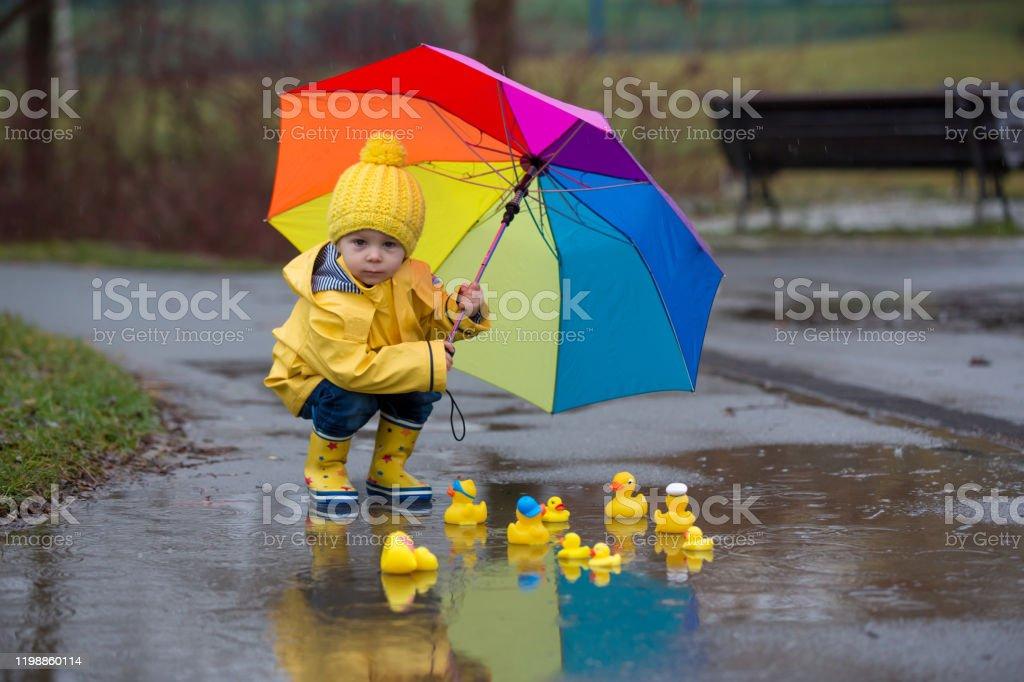 Hermoso niño niño negro rubio divertido con patos de goma y paraguas colorido, saltando en charcos y jugando en la lluvia - Foto de stock de Abrigo libre de derechos