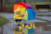 Beautiful funny blonde toddler boy with rubber ducks and colorful umbrella, jumping in puddles and playing in the rain, wintertime