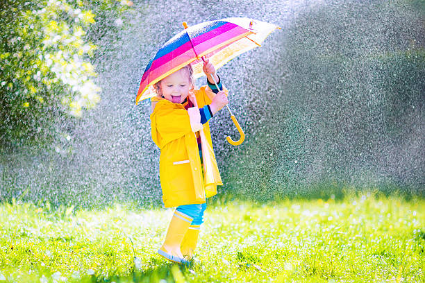 beautiful funny toddler with umbrella playing in the rain - regen zon stockfoto's en -beelden