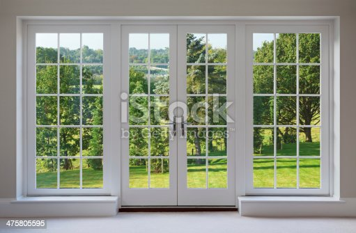 a set of finely crafted wooden Georgian style windows with doors set in a white frame, with white sills and caramel coloured walls. The view through the windows are towards a beautiful  countryside garden.