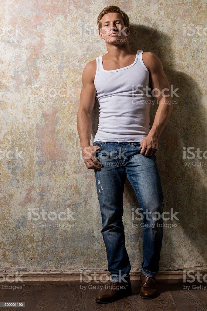 Bellissimo gay in t-shirt bianca in posa contro sfondo grunge - foto stock