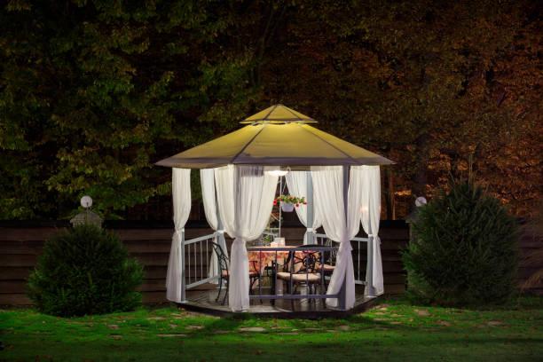 Ein schöner Pavillon mit einer Tabelle in den Abend, Herbst Park wird durch eine Lampe beleuchtet. – Foto