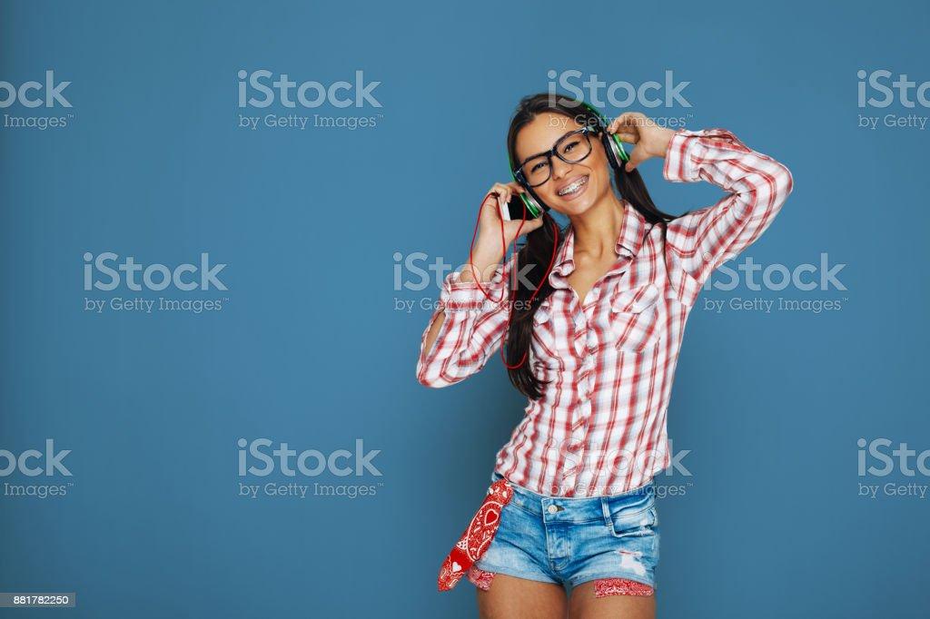 Beautiful geek girl with braces enjoy the music via smart phone stock photo