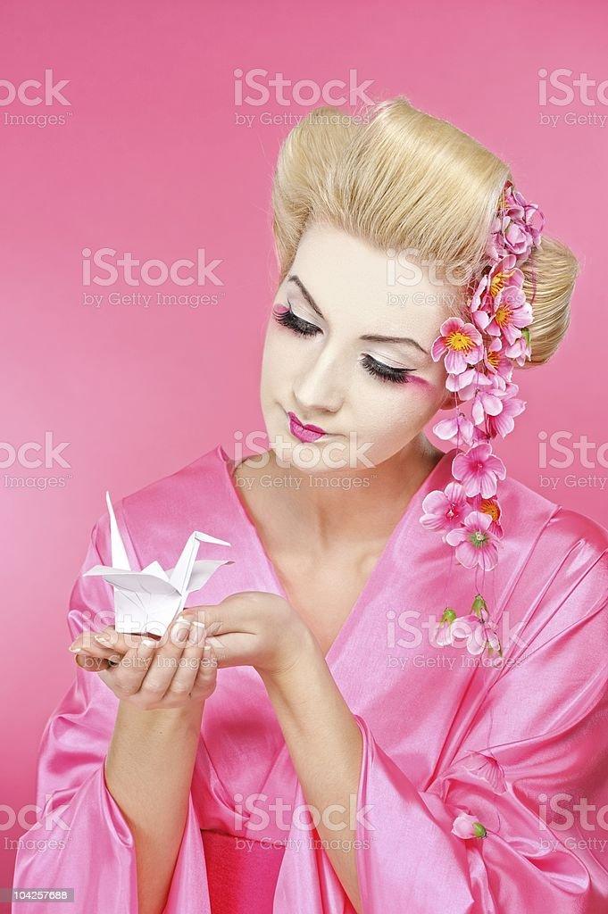 Beautiful geisha holding origami bird royalty-free stock photo
