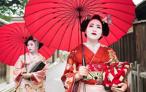 beautiful geishas walking outdoors - natürliche make up kurse stock-fotos und bilder