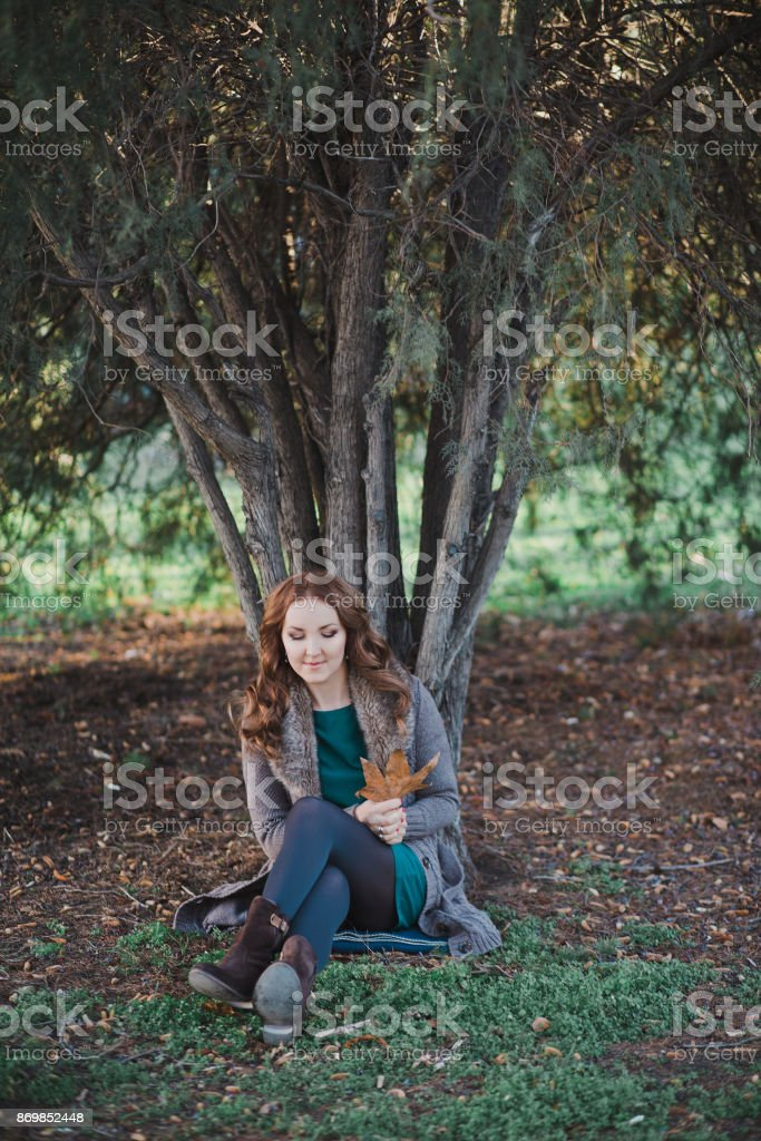 Beautiful genuine lady mystic with curly brunette hairs and adorable eyes dressed in fancy stylish warm clothes with fur on neck lonely posing sit for camera in autumn dark forest stock photo