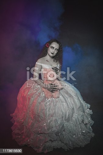 Beautiful ghost woman in white wedding dress with teddy bear. Halloween scene