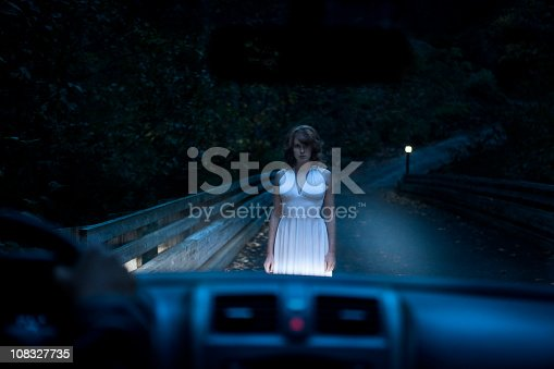 Ghostly female standing outside in front of a car in the middle of the night. View from inside the car. Copy space.